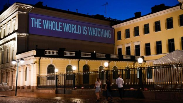 A sentence reading The Whole World is Watching is projected on the presidential palace on the eve of a summit between US President Donald Trump and Russian President Vladimir Putin in Helsinki on July 15, 2018
