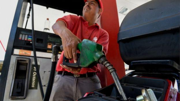 Hombre sirviendo combustible en Caracas.