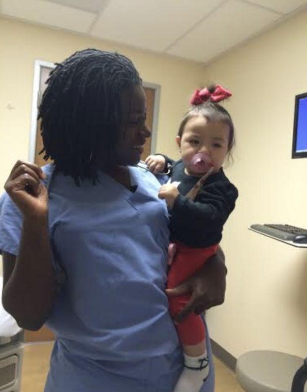 Sarpoma com uma das bebês que ajudou a trazer ao mundo durante a residência em Cuba