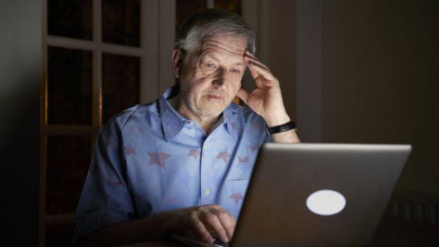 Señor mayor mirando una computadora.