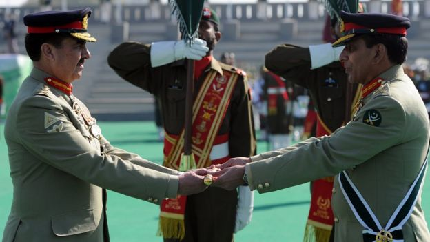 Pakistan's outgoing army chief General Ashfaq Kayani (R) presents the change of command baton to newly-appointed army chief General Raheel Sharif (L) during the change of command ceremony in Rawalpindi on November 29, 2013
