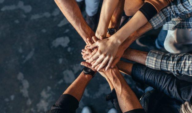 Pessoas colocando mãos umas sobre as outras