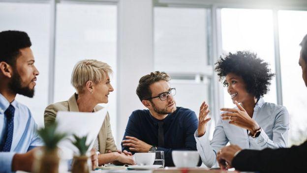 Cinco pessoas sentadas à mesa durante reunião em escritório