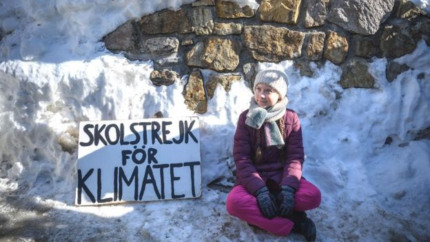"TOPSHOT - Swedish youth climate activist Greta Thunberg sits next to a placard reading ""school strike for climate"" on the sidelines of the World Economic Forum (WEF) annual meeting, on January 25, 2019 in Davos, eastern Switzerland. - Swedish 16-year-old Greta Thunberg has inspired a wave of climate protests by schoolchildren around the world after delivering a fiery speech at the UN climate summit in Katowice, Poland last month. (Photo by Fabrice COFFRINI / AFP) (Photo credit should read FABRICE COFFRINI/AFP/Getty Images)"