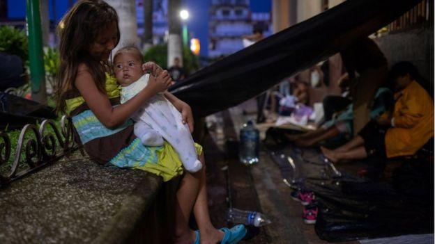 Una niña sostiene a un bebé en la caravana.