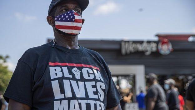 Протестующий стоит у входа в ресторан Wendy'S, который был подожжен после того, как чернокожий человек был застрелен полицейским в пятницу 14 июня 2020 года