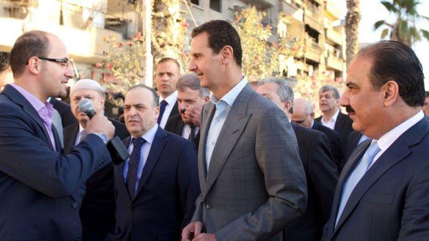 El presidente sirio, Bashar al Assad habla con un periodista durante un recorrido por el barrio de Damasco de Darayya
