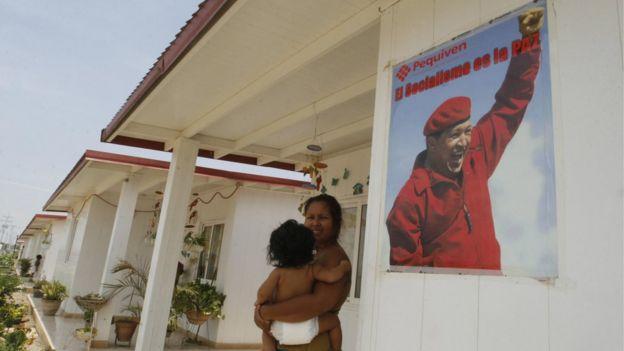 Una mujer frente a una casa con un cartel de Hugo Chávez al lado