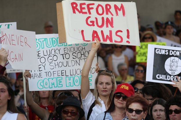 "A woman carries a sign reading ""reform gun laws"", at the rally in Fort Lauderdale"