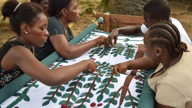 El grupo de costura Quageh en Caldwell, Liberia, recreando el edredón de la planta de café que hizo Ricks.