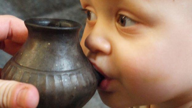 جدید عہد کا ایک بچہ قدیم زمانے کے لوٹا نما برتن کی طرز پر پھر سے بنائے گئے برتن سے دودھ پیتے ہوئے