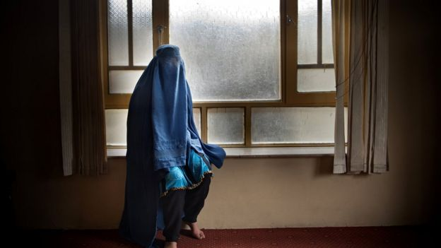 Woman covered with a burqa in a home