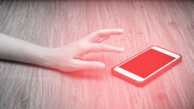 Una mano alcanzando un teléfono en el suelo