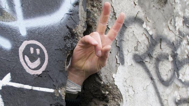 Señal de paz por ranura del muro de Berlín
