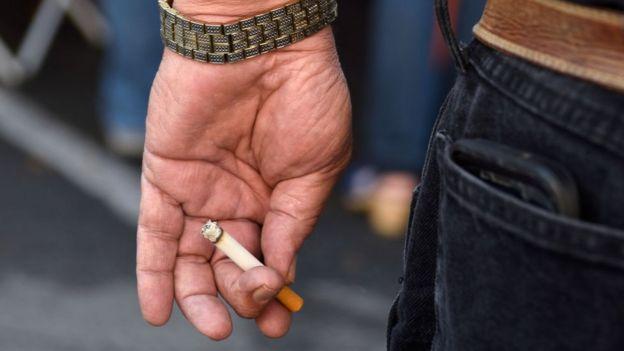 Un hombre sostiene un cigarrillo en su mano.