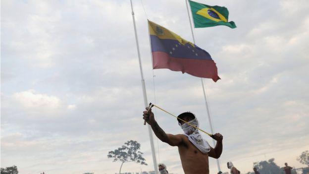brezilya venezuela sınırında sapanla taş atan bir gösterici