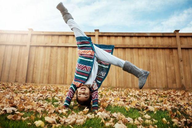 Foto de uma menina dando estrela ao ar livre