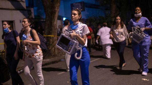 Employees are seen after a fire hit the Badim Hospital in Rio de Janeiro, Brazil September 12, 2019