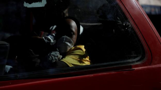 "A boy wearing protective gloves and a mask travels in a van, after Haiti""s government declared a state of emergency"