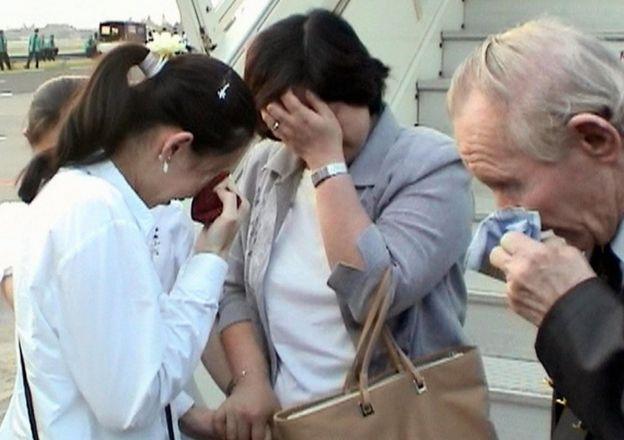 Hitomi Soga, Charles Jenkins y su hija Mika se secan las lágrimas cuando se reencuentra en el aeropuerto de Yakarta, Indonesia, en julio de 2004