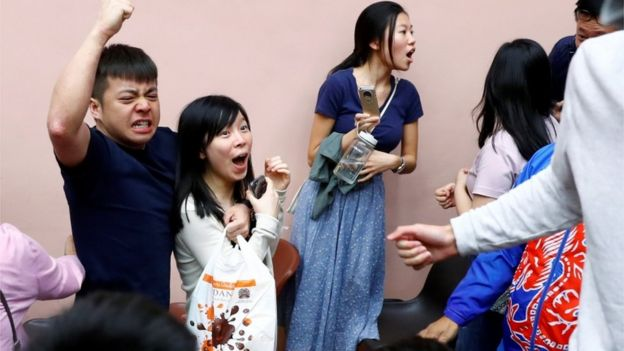 Supporters of local candidate Kelvin Lam celebrate after he wins his race in Hong Kong