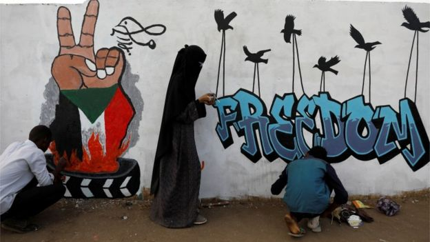 "Demonstrators in Khartoum paint a mural reading ""Freedom"", 14 April 2019"
