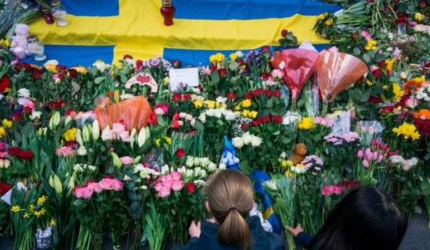 Women lay flowers on April 9, 2017 at a makeshift memorial near the point where a truck drove into a department store in Stockholm, Sweden