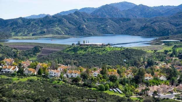 In the mountains of Santa Monica, houses and fields are located near the mountain lake