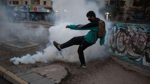 Manifestante se enfrenta a las fuerzas de seguridad durante las protestas del 27 de abril en Santiago de Chile.