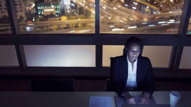 Mulher digita em laptop durante a noite, com vista da janela de rua movimentada de carros