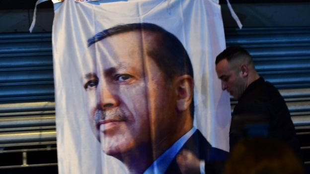 Un hombre camina frente a un banner con el rostro de Erdogan.