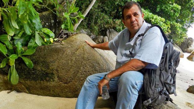 约翰在马赫岛的岩石上寻找他认为的海盗标记