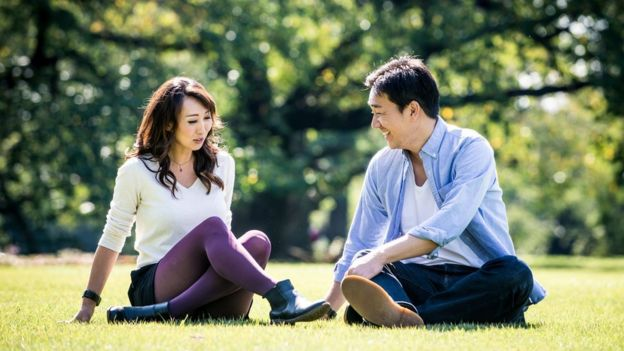 Japanese couple, sitting on the grass at a park in Tokyo, Japan