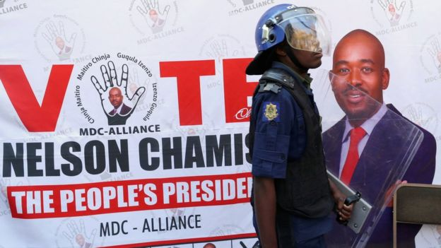 A riot police officer in front of an MDC Alliance poster in Harare, Zimbabwe