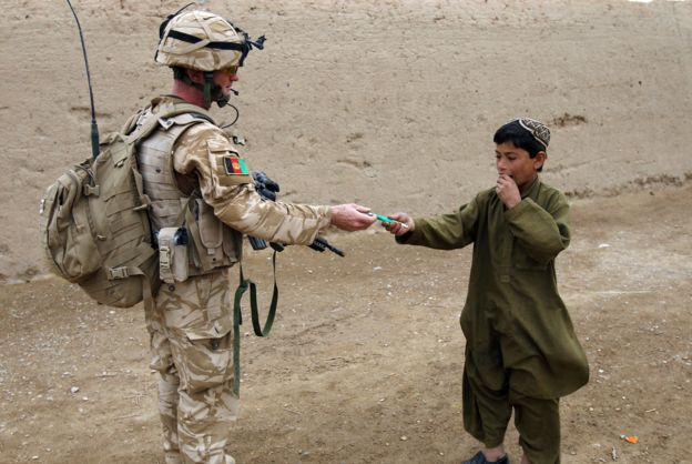 A British soldier of the 1st batallion of the Royal Welsh gives a pen to an Afghan boy during a patrol in the streets of Showal in Nad-e-Ali district, Southern Afghanistan, in Helmand Province on February 25, 2010. Some 400 UK soldiers are mobilized to fight in the Mustarak (Together) operation. Combined forces of 15,000 US, NATO and Afghan troops are facing stiff resistance in pockets of Helmand province where they are battling to eradicate Taliban fighters who have controlled the area with drug lords for years. AFP PHOTO/Thomas COEX (Photo credit should read THOMAS COEX/AFP/Getty Images)