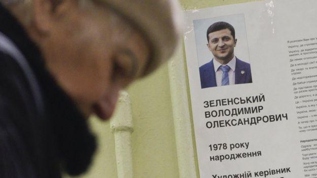 Жінка на виборчій дільниці, біля портрета Володимира Зеленського