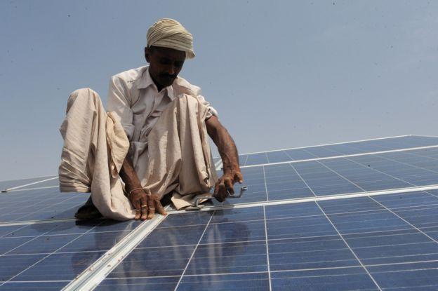 Um trabalhador instala painéis solares no parque solar Gujarat em Patan, Índia