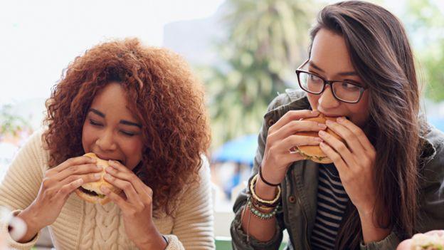 Duas mulheres comendo hambúrgueres