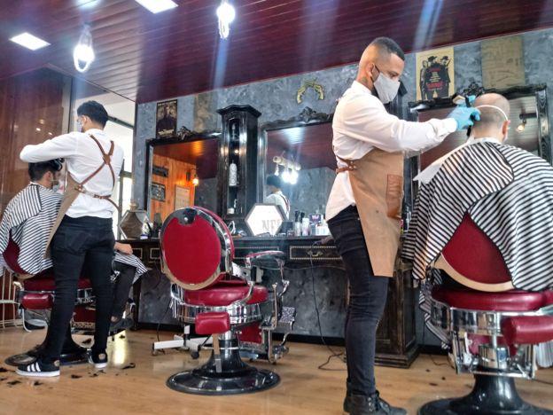 Barbeiros cortam cabelo de clientes