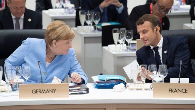 Angela Merkel e Emmanuel Macron se falam durante cúpula, em que aparecem sentados e com placas de seus respectivos países: Alemanha e França
