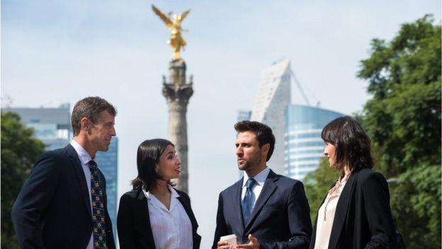 Hombres y mujeres de negocios blancos ante el Ángel de la Independencia de CDMX.