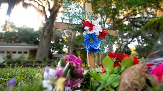 Flores y una cruz en el lugar donde murió Ahmaud Arbery