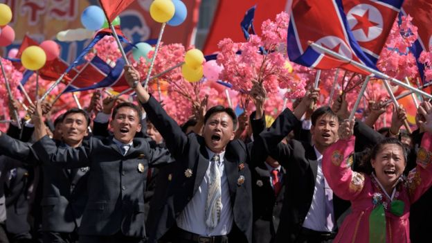 parade participants wave flowers as they pass Mr Kim