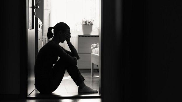 Mujer sentada en el suelo blanco y negro.