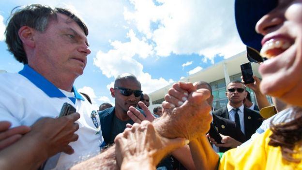 President Jair Bolsonaro shakes hand with a supporter on 15 March, amidst the Covid-19 outbreak in Brazil, 15 March