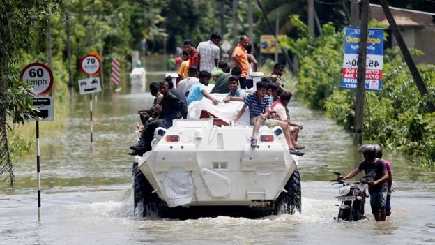 People are transported on top of an armoured personnel carrier on a flooded road in Sri Lanka