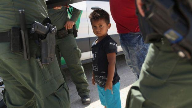 Un niño migrante, rodeado de agentes de la Patrulla Fronteriza.