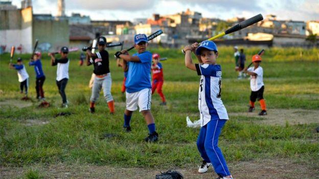 Niños cubanos juegan béisbol