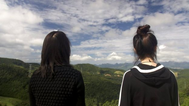 Now safely over the border Mira (L) and Jiyun (R) look out over a mountain range back towards China