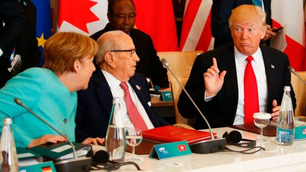 U.S. President Donald Trump talks to German Chancellor Angela Merkel and Tunisia's President Beji Caid Essebsi